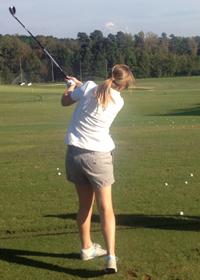 A Fuqua student driving a golf ball