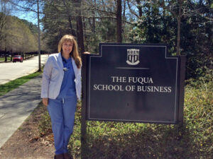 Anne Steptoe, Duke MBA entrepreneur, beside the Fuqua sign