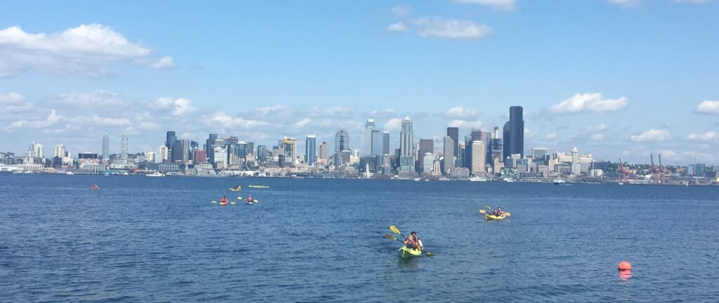 kayaks on the water with the city skyline in the background Kayaking, internship in Seattle