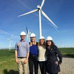 4 Fuqua interns pursuing an energy career posing on a wind farm
