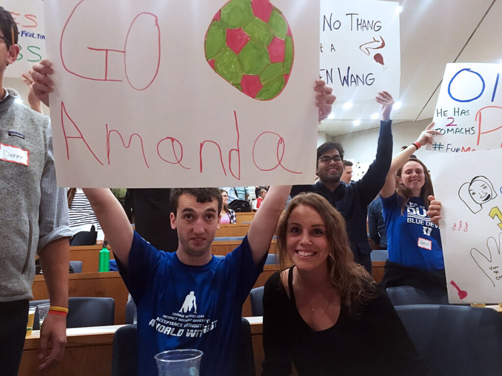 Stephanie and a Special Olympian holding up a sign at the MBA games fundraiser