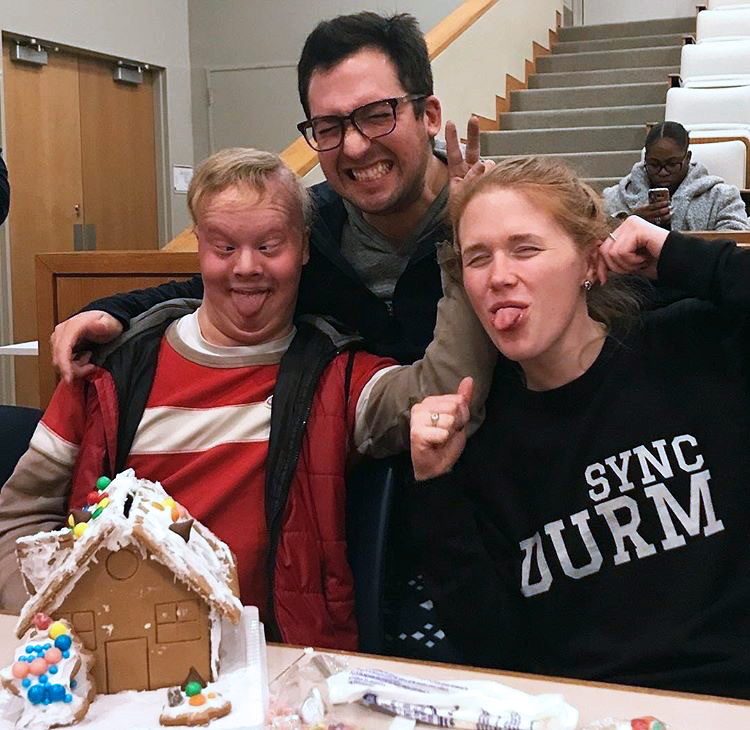 Students and a Special Olympian being silly while building a gingerbread house during an MBA games event