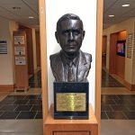 a bust of J.B. Fuqua in the school hallway