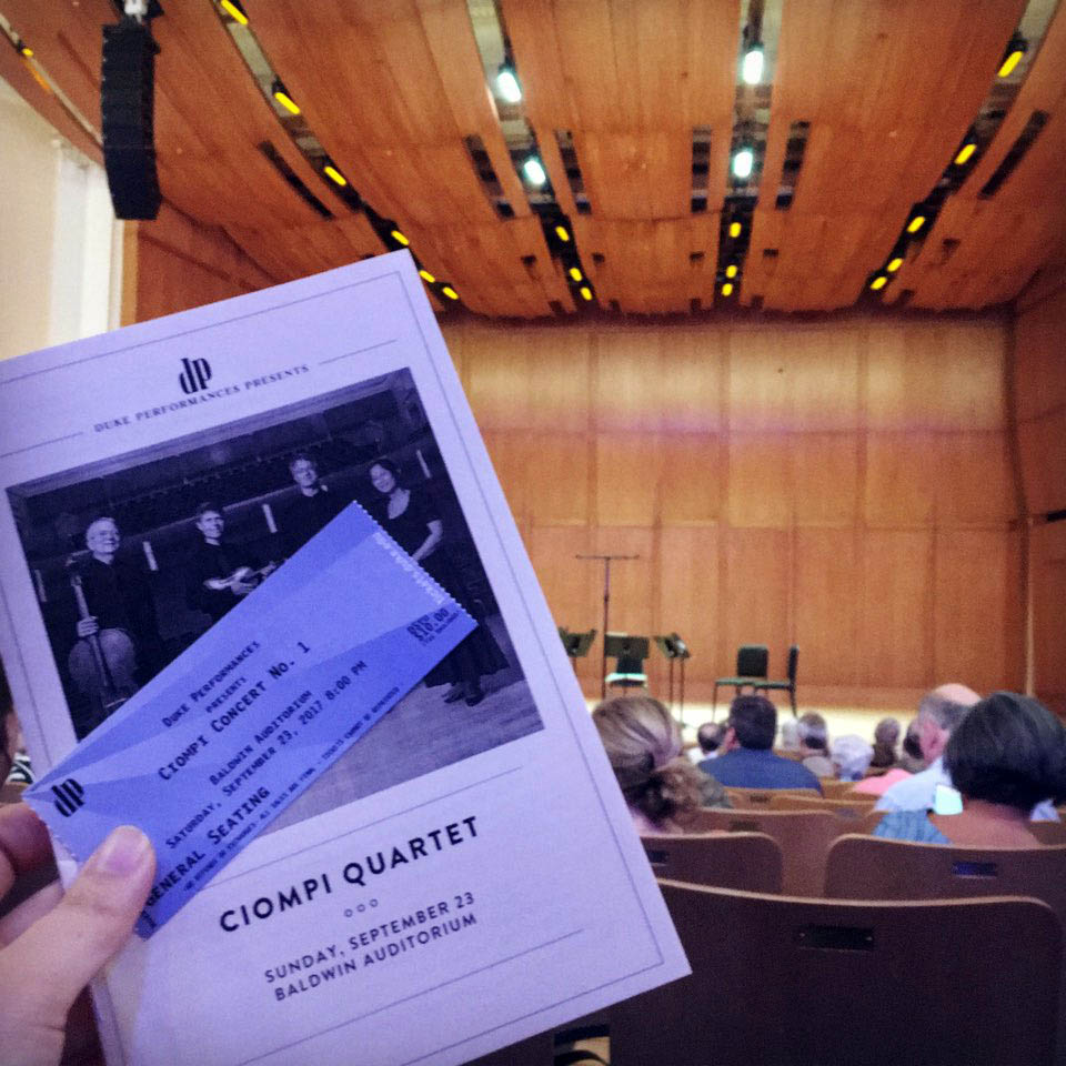 a ticket and program for a Ciompi Quartet concert with the stage in the background, a scene from exploring the Duke community beyond Fuqua