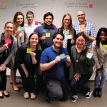 10 students posing with messages written on sticky notes as part of a design thinking exercise