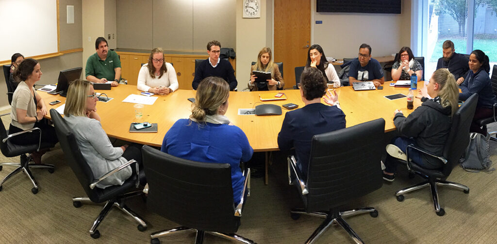 A mix of students and staff convene around a conference table, MBA student leader