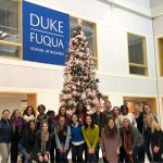 two dozen students, mostly comprised of some of the women at Fuqua, post in front of the school's Christmas tree