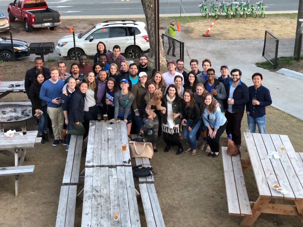 three dozen students, mostly comprised of some of the women at Fuqua, pose for a photo in the beer garden at Ponysaurus Brewing