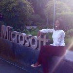 Tiffany sitting beside the Microsoft sign during her Microsoft internship