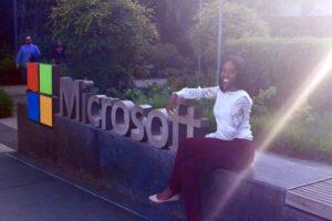 Tiffany sitting beside the Microsoft sign during her Microsoft internship