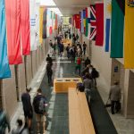 dozens of flags line the hallway with students bustling below, international student