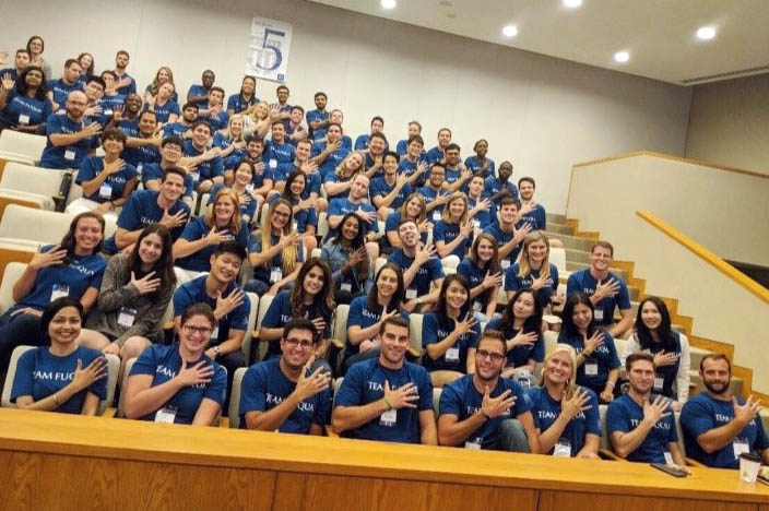 Class sections: about 70 students in section 5 holding up 5 fingers during orientation