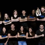 11 students pose with messages written on their arms about their interest in pursuing a social impact career