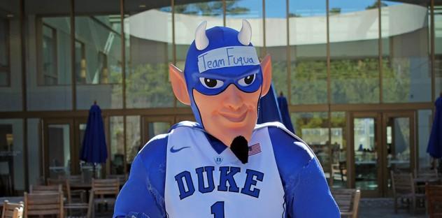 "Duke University's Blue Devil mascot holding a ""Team Fuqua"" pennant flag at BDW"