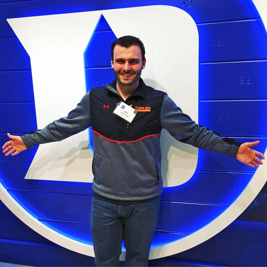 "An admitted student in a University of Maryland shirt posing in front of a Duke ""D"" in Cameron Indoor Stadium during BDW"