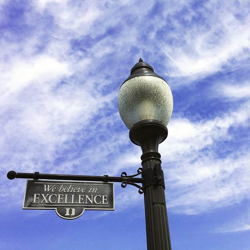 "a Duke lamp post sign that reads ""We believe in excellence"""
