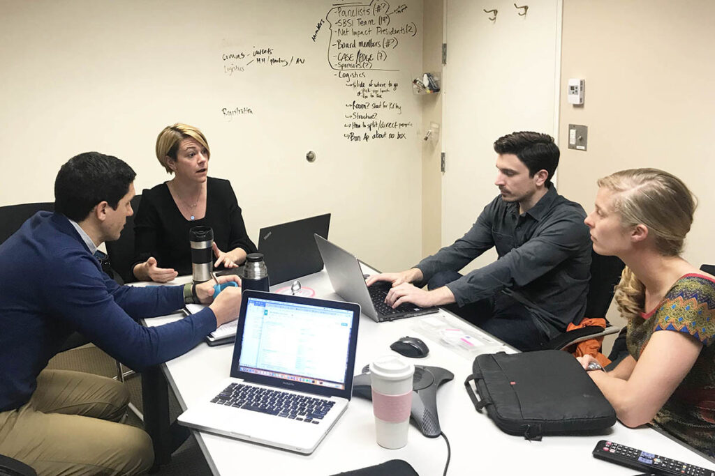 Erin and students in a discussion, seated at a conference table with laptops out and notes about the social impact conference on the white board