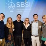 Erin posing on stage with student leaders and speakers from the social impact conference