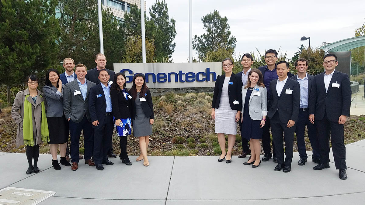 15 students in business attire posing beside the Genentech sign, one of my favorite Fuqua memories