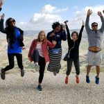 7 students leaping for joy with mountains in the background, one of my favorite Fuqua memories