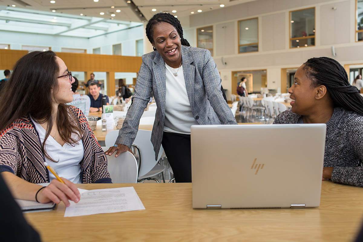 Professor Ashleigh Rosette, instructor of Fuqua's women in leadership course, chatting with two students in the Fox Center