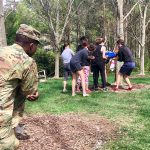 a soldier looks on as a handful of student work together to make their way through a 'spiderweb' obstacle during leadership development exercises