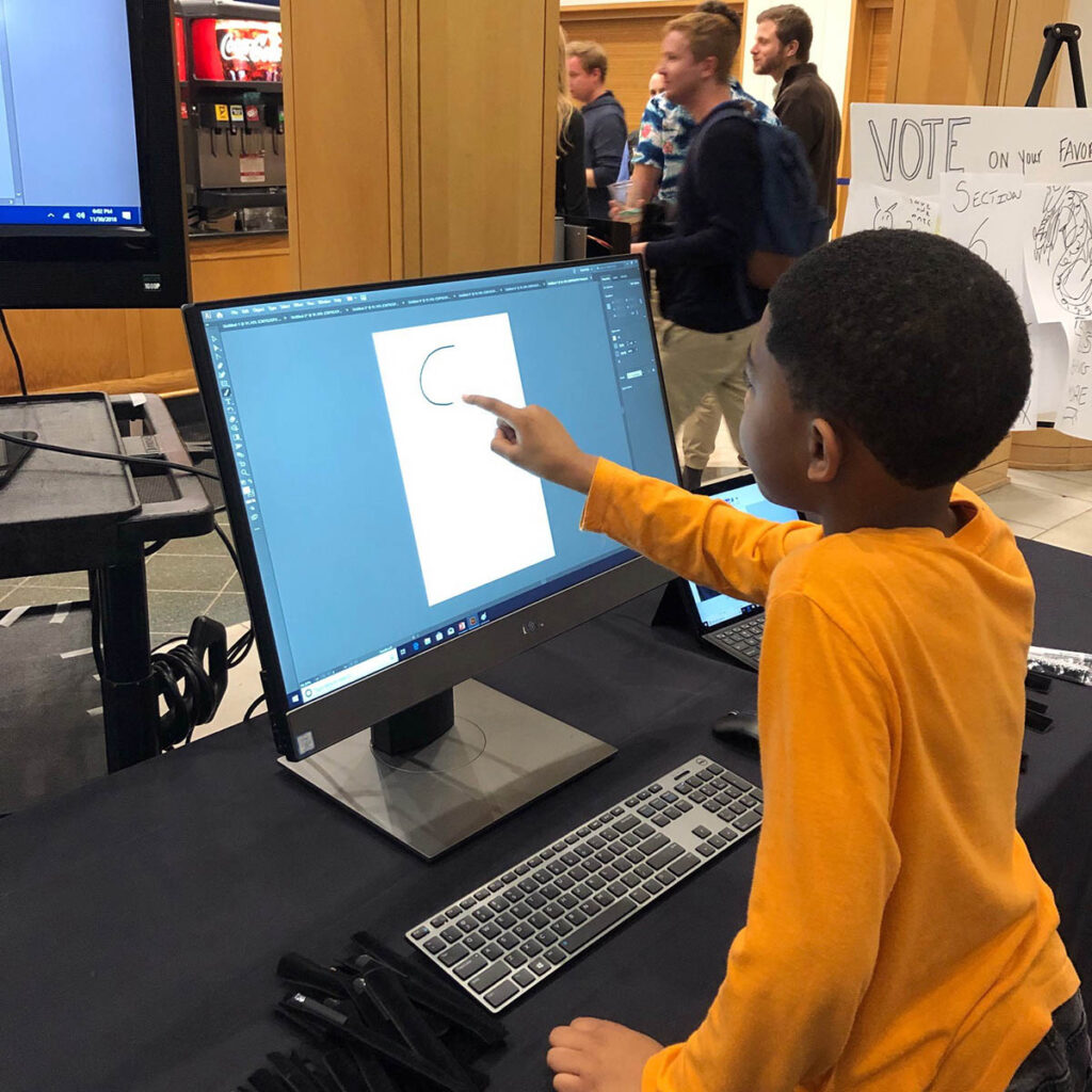 A young boy using his finger on the computer screen to draw