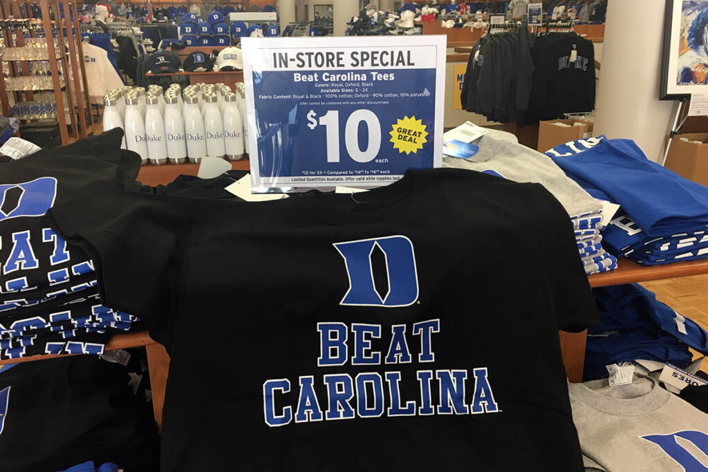 "A Duke-UNC rivalry shirt that reads ""Beat Carolina"" on a merchandise table for sale display"