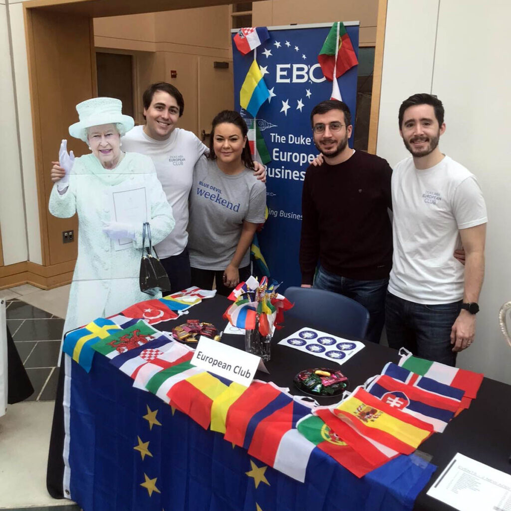 four students and a life-sized cut out of Queen Elizabeth II stationed at an info booth; advice for European applicants