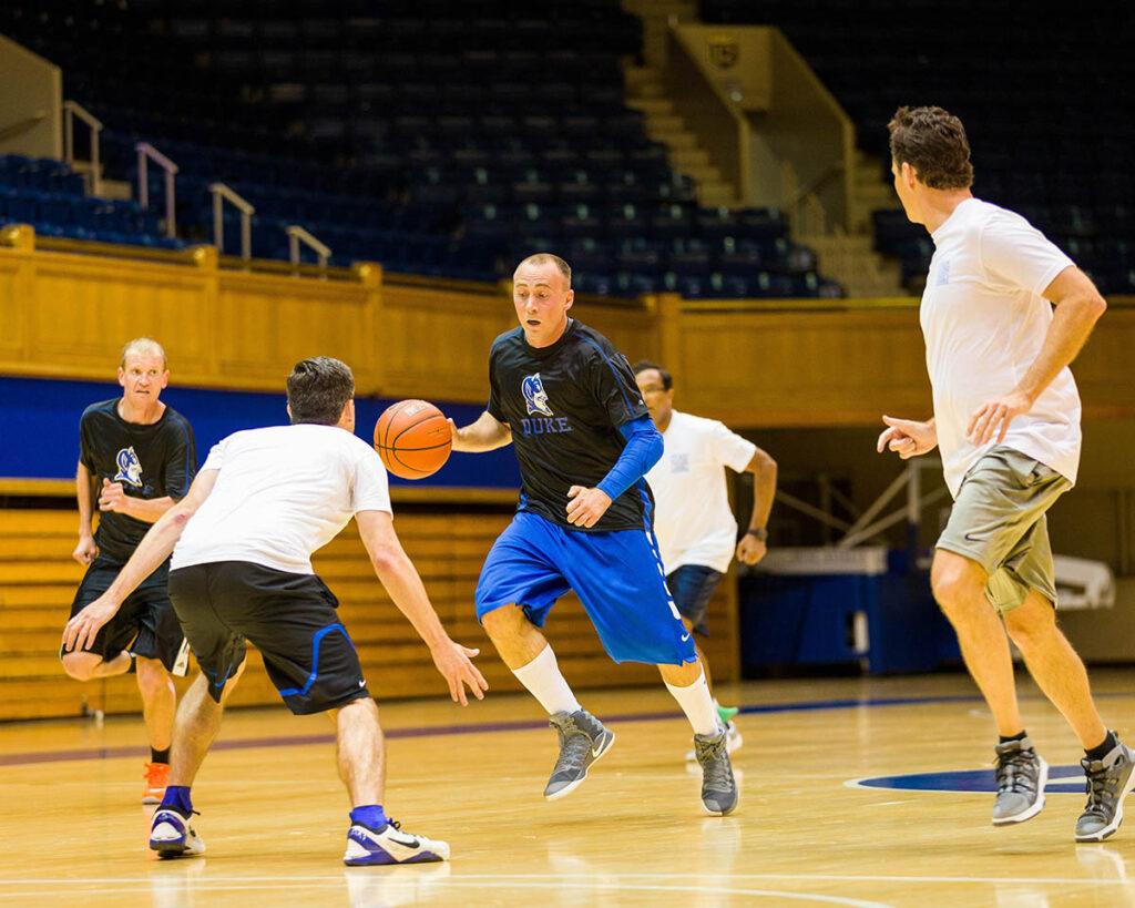 Kevin Kumlien driving down the basketball court against his buddy Steve Misuraca inside Cameron Indoor Stadium