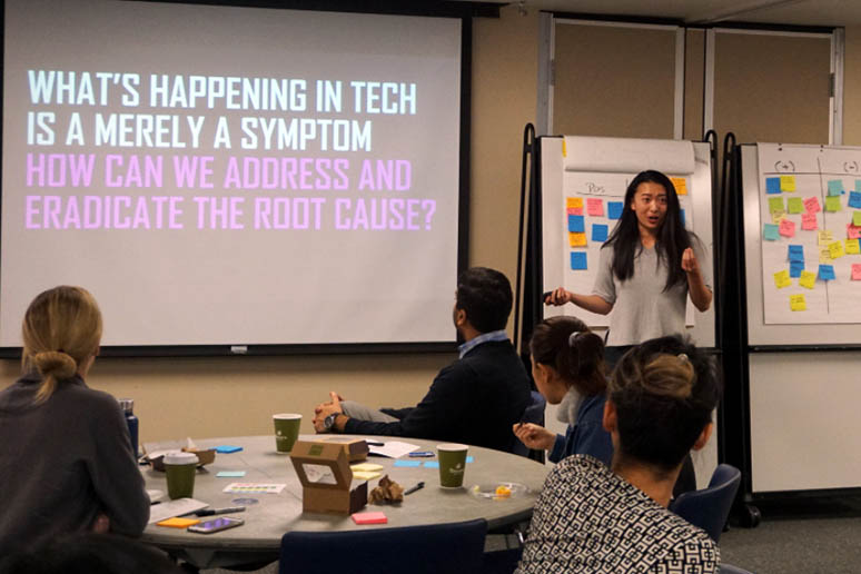 Kat Zhou in the front of the room presenting during a Design + Innovation Club event