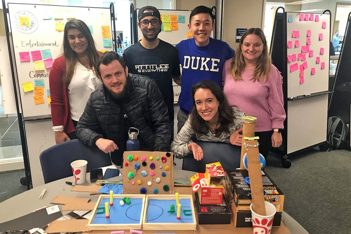 six students at a table with various craft and design supplies during a Design + Innovation Club event