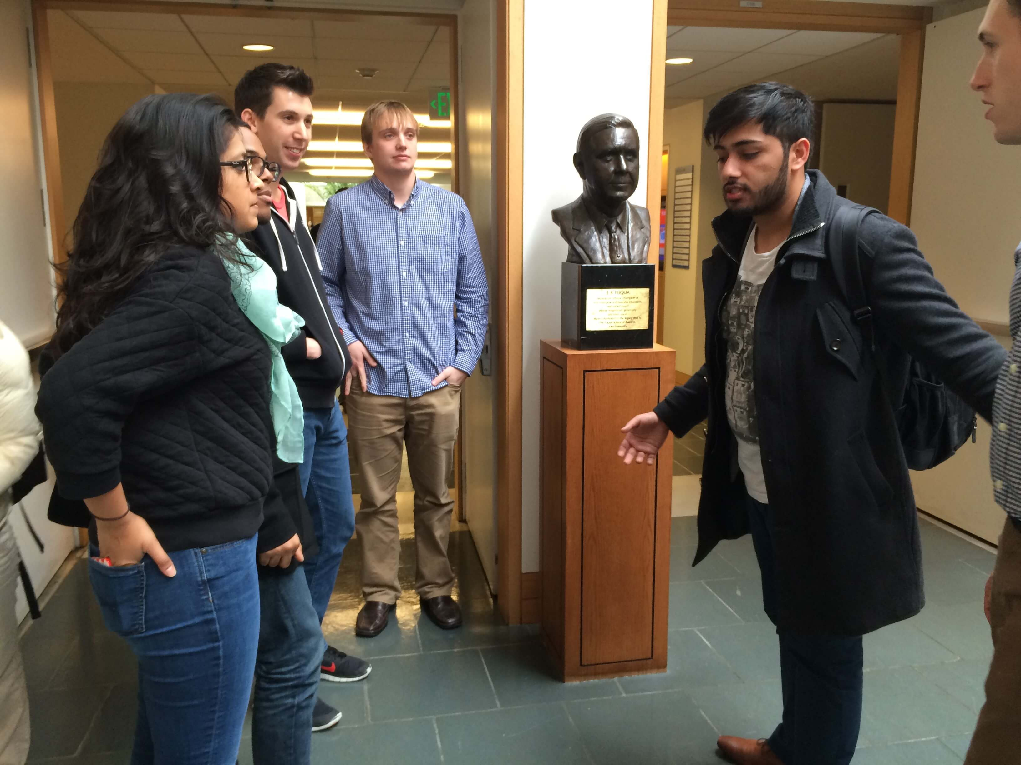 Admissions Ambassadors pause at the bust of school namesake, J.B. Fuqua, to tell his story