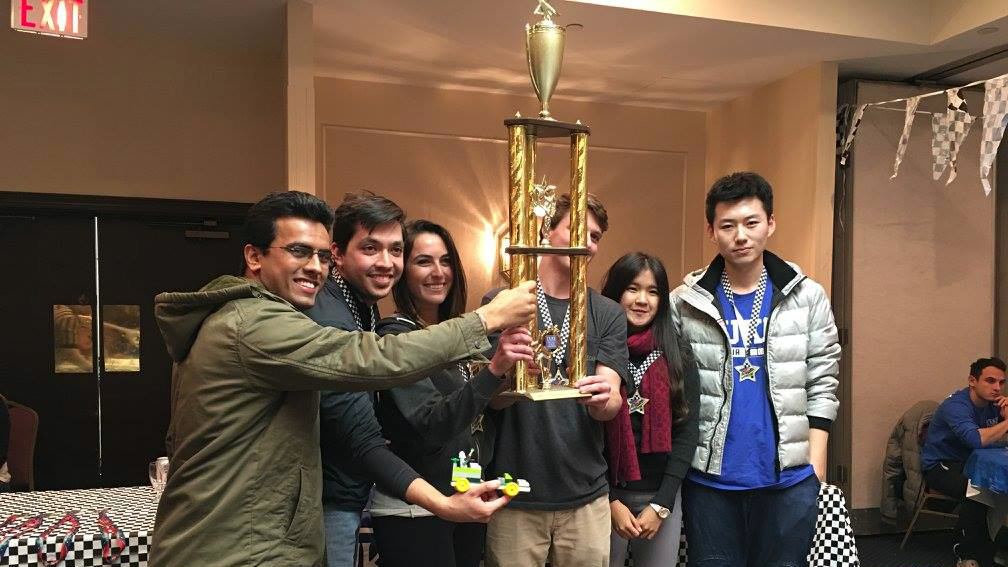 the winning student team holds up the trophy, Team Fuqua