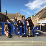 students posing around a Duke sign, questions to ask when considering graduate school