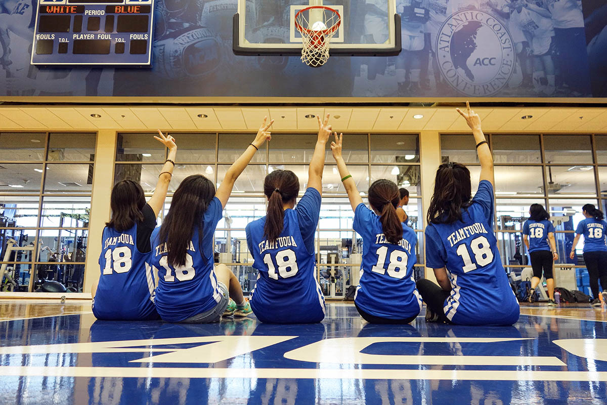 Five classmates sitting on a basketball court during the Duke basketball experience, Why MMS among other graduate school options
