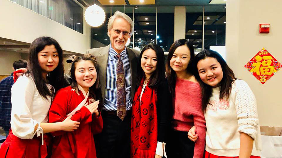 Dean Bill Boulding posing for a group photo with five East Asian international students