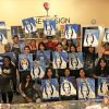 a dozen students displaying the Blue Devil paintings they created during a Wine and Design event, 25 Random Things