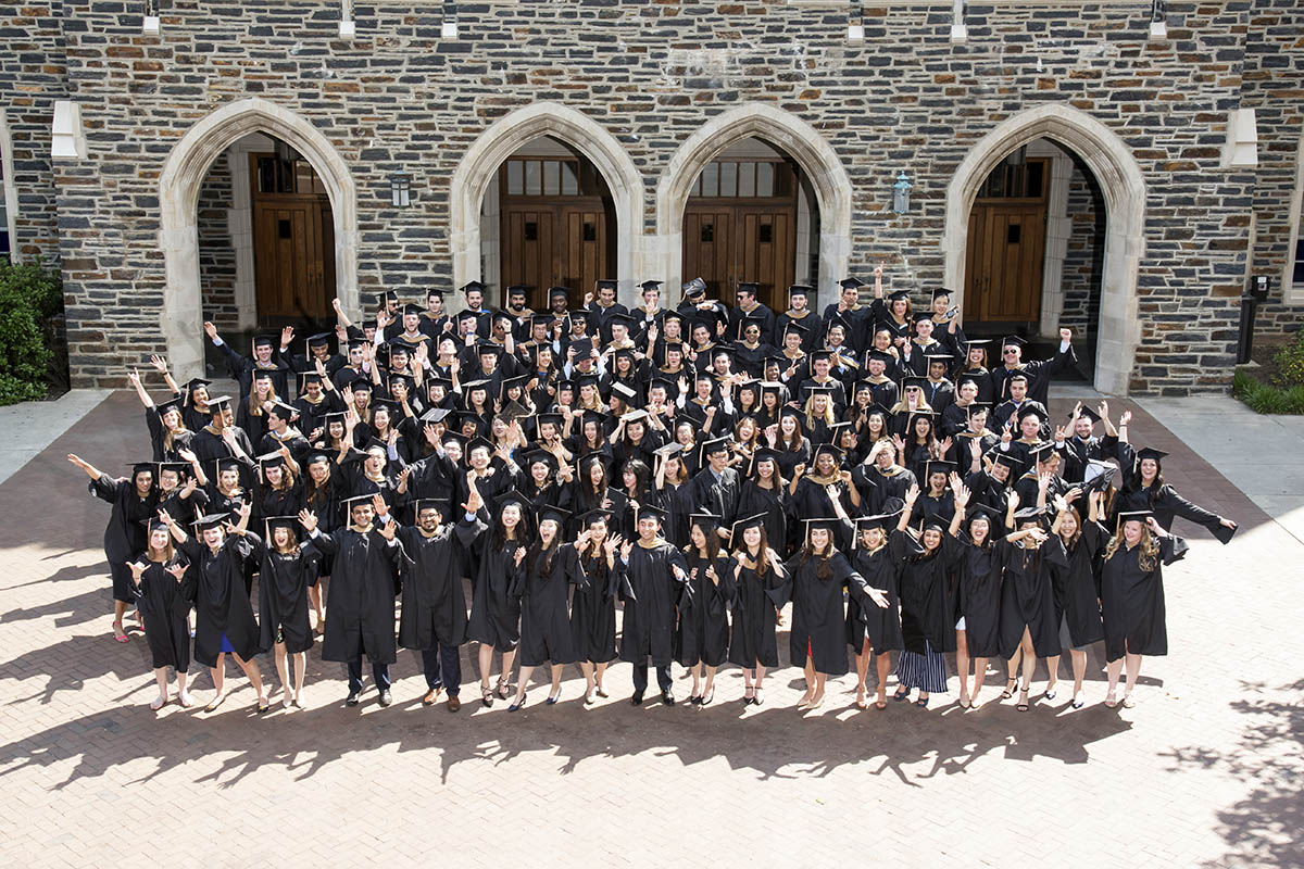 the entire class of 2018 in their gowns at commencement posing for a group photo and throwing their caps into the air; MMS employment outcomes
