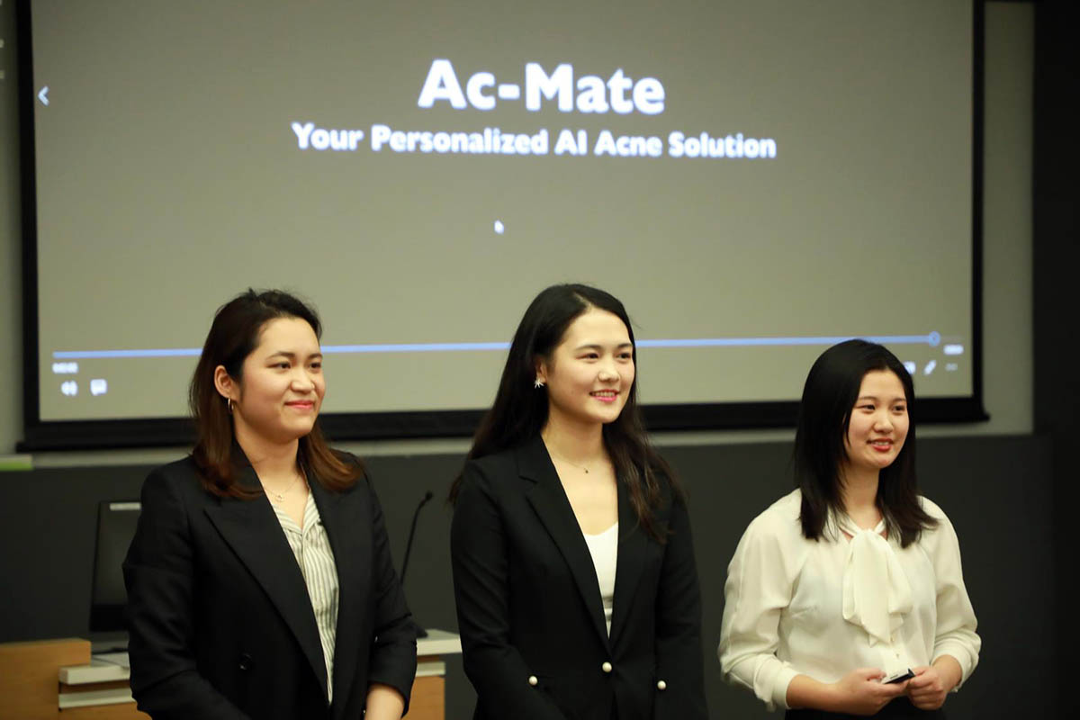 the three students presenting in front of a projection screen; marketing experience