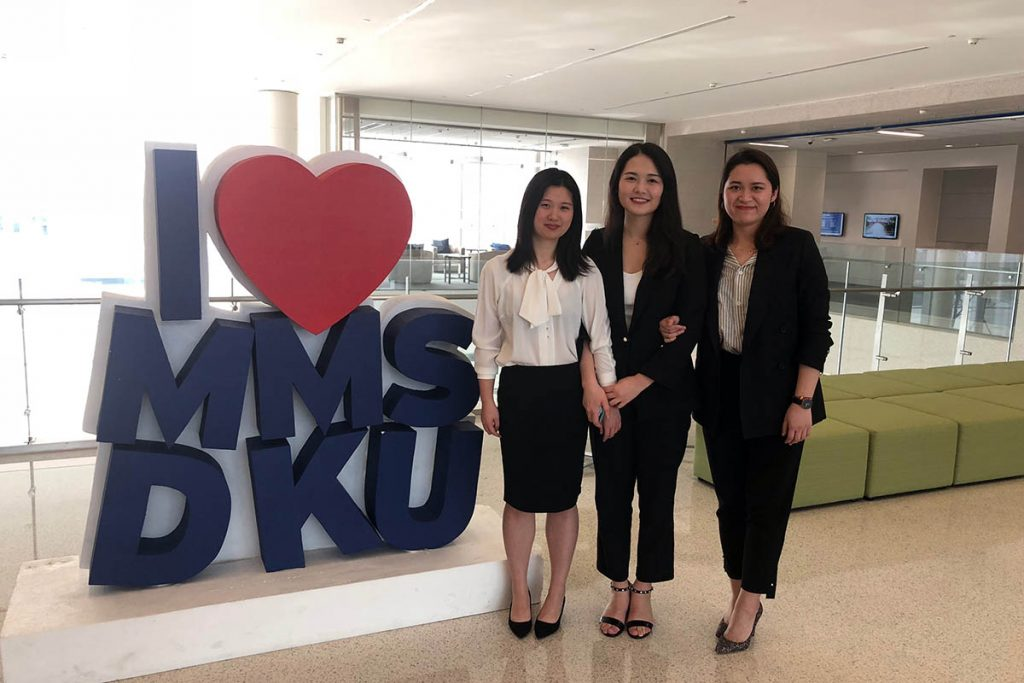 "marketing experience; the three students posing in front of a sign that reads ""I Love MMS: DKU"""