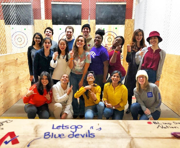 15 students post for a photo in an ax throwing range during one of their student events