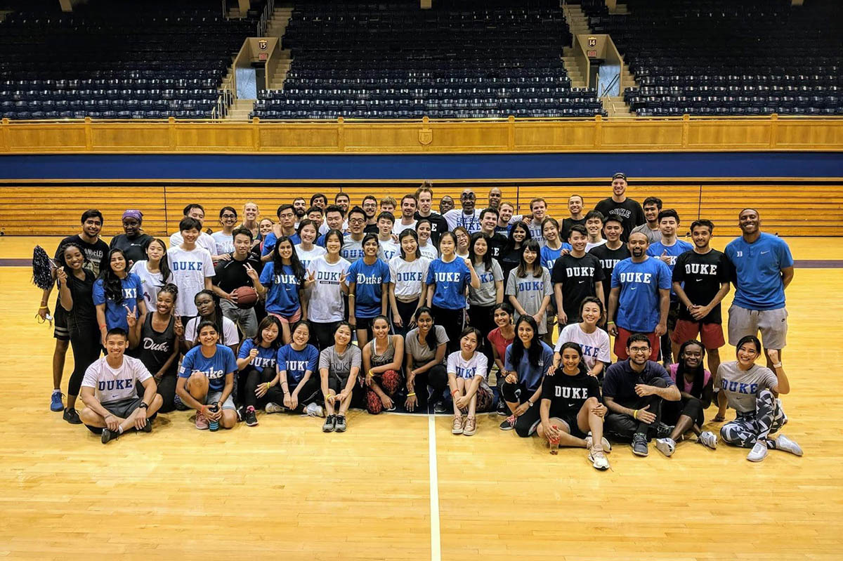 about 100 students pose for a group photo with Duke basketball coaches on the Cameron Indoor Stadium court during one of their student events