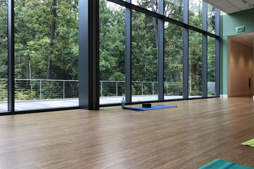 A floor with yoga mats on it faces a wall of windows looking out at trees, one of the places to exercise at Duke