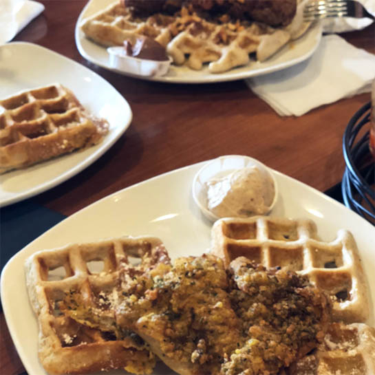 plates of waffles, one of which is topped with fried chicken, from Dame's one of Lily's brunch recommendations