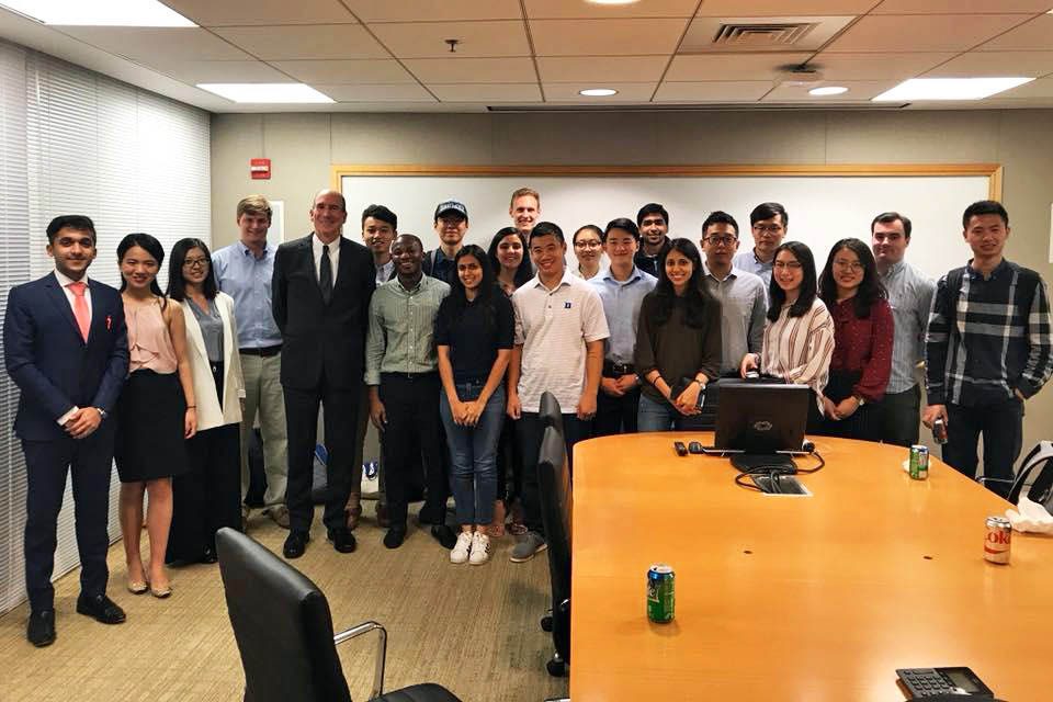 close to 20 students pose for a photo with Professor John Buley during a finance interest group session, one of the extracurriculars at Fuqua