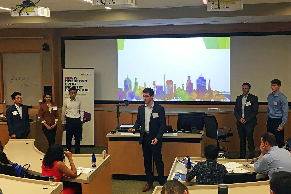 John and his team presenting at the front of a classroom during the Accenture case challenge
