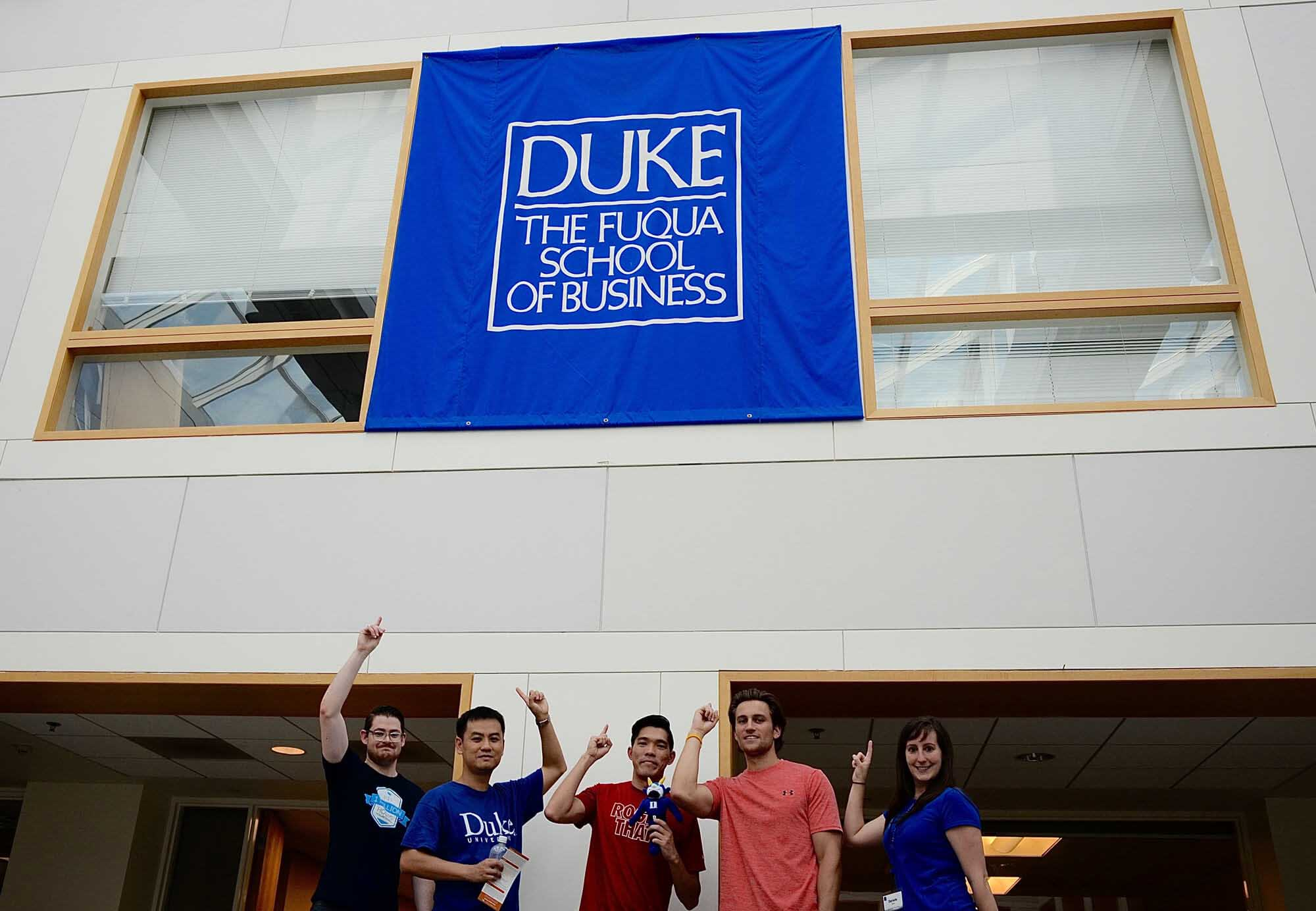 Duke Cross Continent MBA students posing under the Fuqua banner