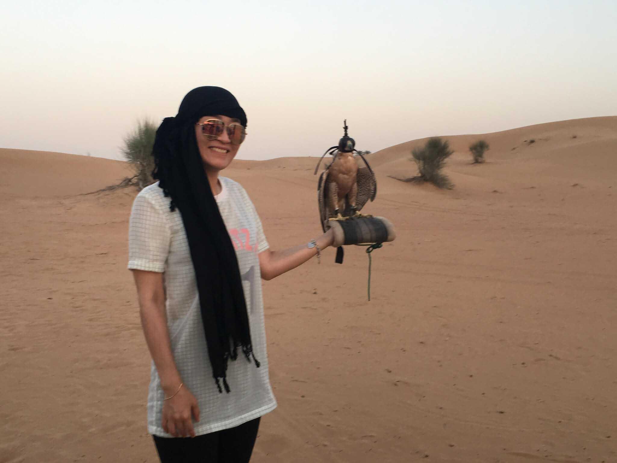 Student holding a bird in a Dubai desert