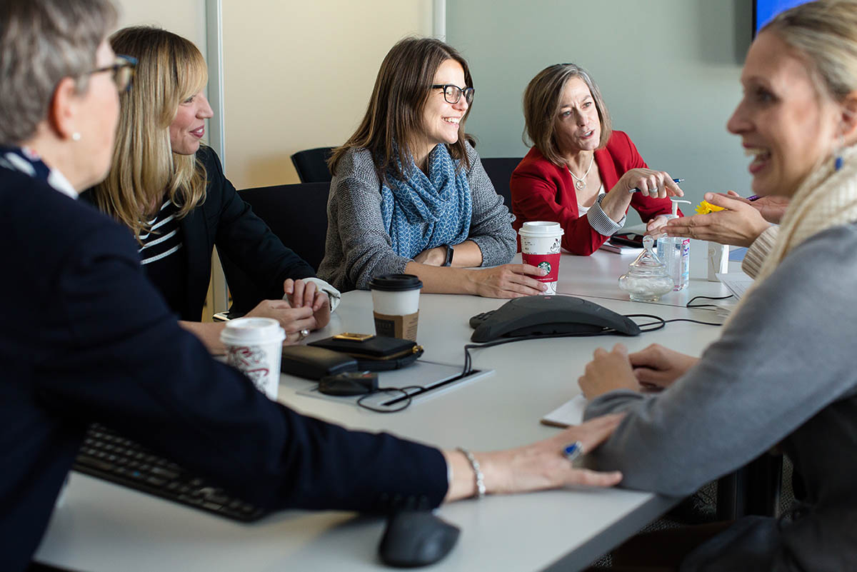 five members of the career management center chat around a conference table